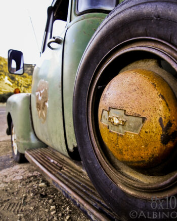Driver side photo of rusted chevy pickup with spare tire, American landscape